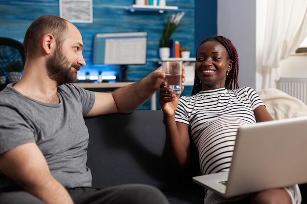 Coppia sposata interrazziale in attesa di un bambino a casa. uomo caucasico che porta bicchiere d'acqua al computer portatile della holding della donna afroamericana incinta. partner multietnici con gravidanza