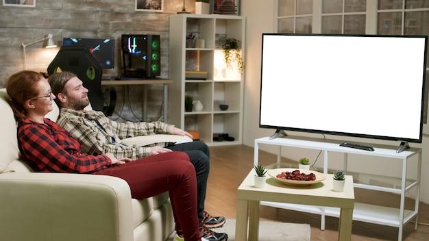 Coppia giovane sposata che si rilassa sul divano guardando la tv con schermo verde.