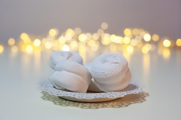 Marshmallow su un piatto sul tavolo sullo sfondo delle ghirlande di luci di natale