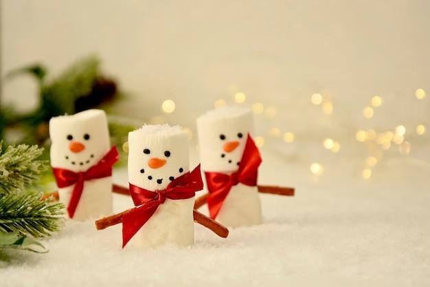 Marshmallow snowmen christmas con bokeh e rami di abete
