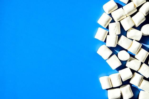 Marshmallow su sfondo blu con spazio di copia. disposizione piatta. vista dall'alto. sfondo o trama di mini marshmallow colorati. concetto di sfondo cibo invernale. cibo spazzatura malsano.