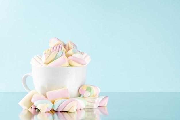 Marshmallows caramelle gommose colorate in una tazza sull'azzurro.