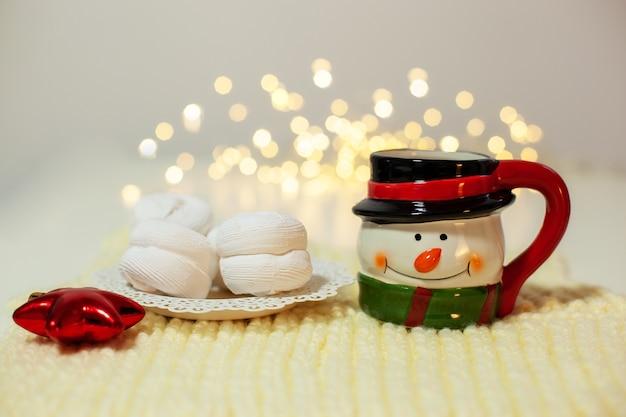 Marshmallow e tazza di pupazzo di neve con cacao per babbo natale su sfondo di luci