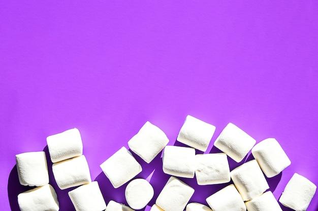 Marshmallow su sfondo viola con spazio di copia. disposizione piatta. vista dall'alto. sfondo o trama di mini marshmallow colorati. concetto di sfondo cibo invernale. cibo spazzatura malsano.