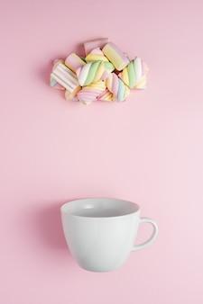 Marshmallow a forma di nuvola piovosa con tazza bianca sul rosa.