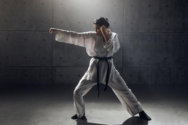 Concetto di arti marziali. giovane donna in kimono che pratica karate