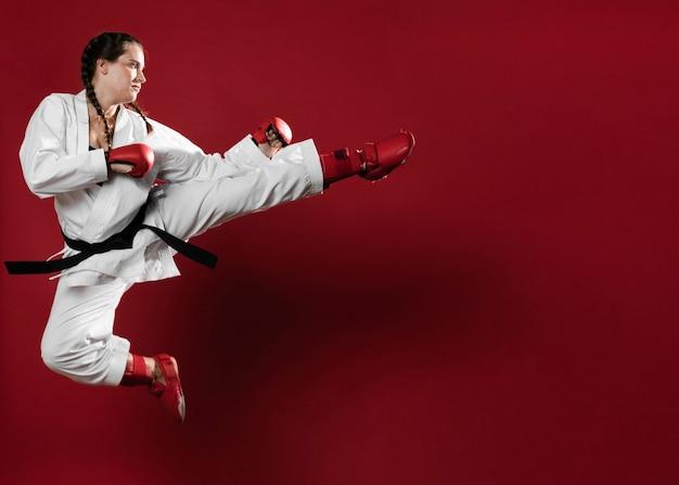 Ragazza di karatè di arti marziali con il fondo dello spazio della copia e della cintura nera Foto Premium