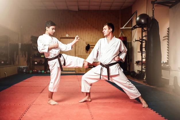 Maestri di arti marziali in kimono bianco e cinture nere, pratica di autodifesa in palestra