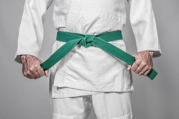Praticante di arti marziali che stringe la cintura con entrambe le mani. dettaglio e concetto di sport.