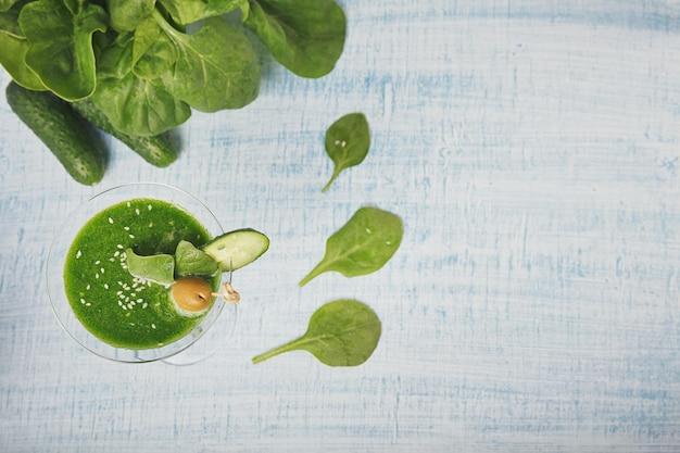 Bicchiere da martini riempito con spinaci verdi freschi e frullato di cetriolo su fondo di legno azzurro. bevande analcoliche. cibo sano e concetto vegetariano.