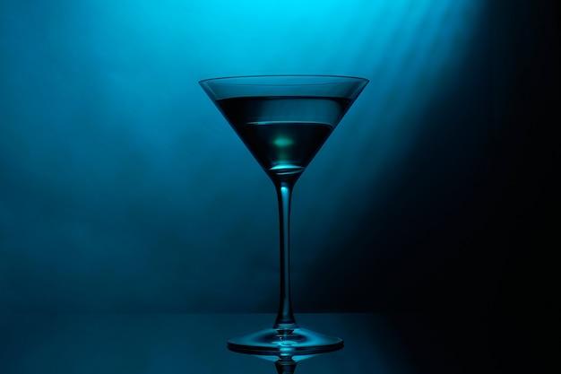 Bicchiere da martini con colore blu su fondo nero.