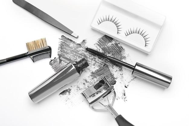 Mascara con ciglia finte e strumenti su bianco