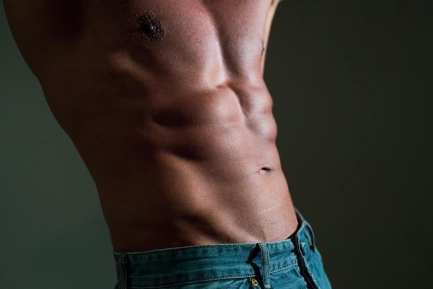 Corpo duro maschile. uomo di forma fisica che mostra addominali scolpiti su sfondo grigio.