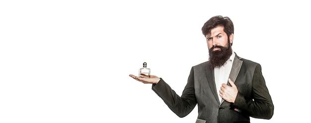Profumo maschile, uomo barbuto in completo. maschio che sostiene una bottiglia di profumo. profumo uomo, fragranza