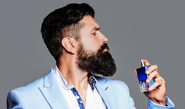 Profumo maschile, uomo barbuto in abito. maschio tenendo in mano una bottiglia di profumo.