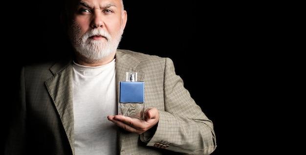 Profumo maschile, vecchio barbuto in completo. maschio che sostiene una bottiglia di profumo. profumo uomo invecchiato, fragranza. profumo o bottiglia di colonia profumeria, cosmetici, bottiglia di profumo, colonia maschile.