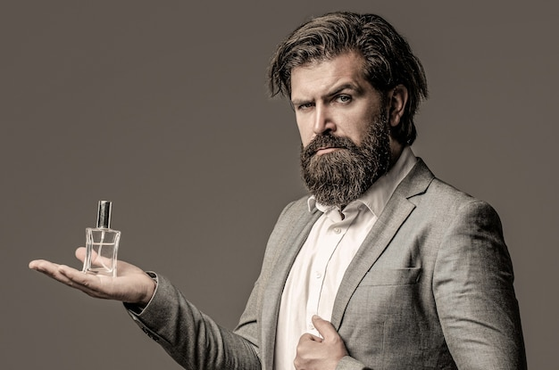 Profumeria maschile, uomo barbuto in completo. maschio che sostiene una bottiglia di profumo. profumo uomo, fragranza. bottiglia di profumo o colonia, profumeria, cosmetici, bottiglia di colonia profumata, colonia di contenimento maschile.