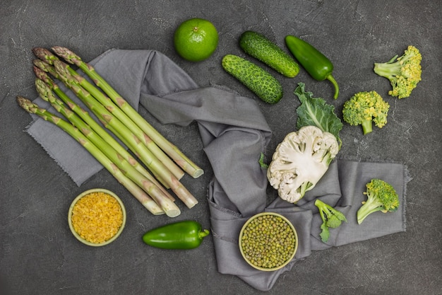 Mash e bulgur in ciotole. asparagi, metà cavolfiore, broccoli su tovagliolo grigio. cetrioli e peperoni sul tavolo. sfondo nero. lay piatto