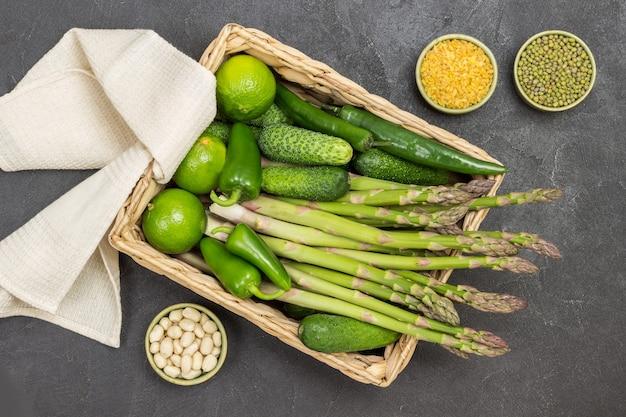 Mash, bulgur e noci in ciotole. asparagi, cetrioli e lime in cestino di rattan. tovagliolo beige. sfondo nero. lay piatto