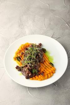 Purè di carote con carne di manzo e verde su sfondo di cemento
