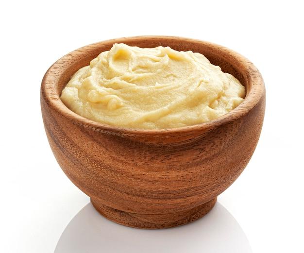 Purè di patate in una ciotola di legno isolato su bianco, purea di verdure