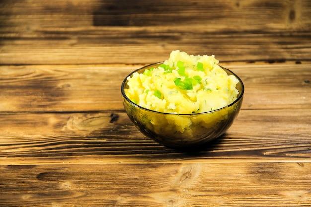 Purè di patate in una ciotola di vetro sul tavolo di legno