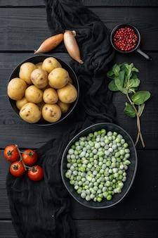 Ingredienti di purè di patate con piselli e menta, laici piatta, sul tavolo di legno nero