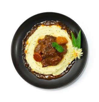 Purè di patate in cima con stufato di manzo in salsa al vino rosso piatto principale delizioso cibo europeo decorazione in stile verdure intagliate vista dall'alto