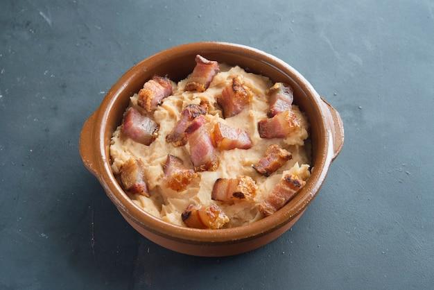 Purè di patate con fetta di pancetta