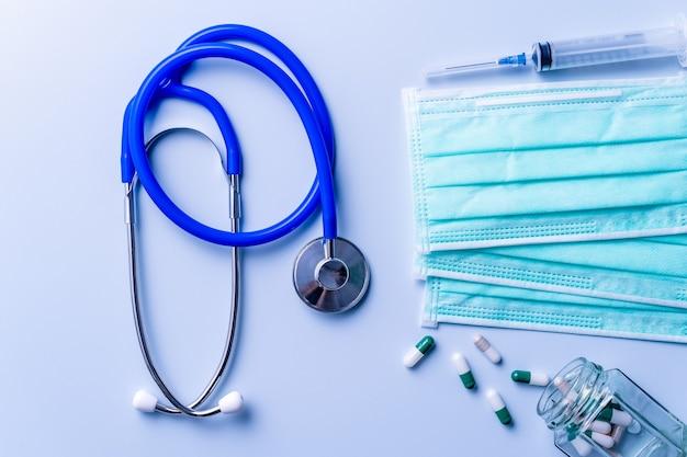 Maschera con pillole, stetoscopio, oggetti di forniture mediche per siringhe isolati su sfondo blu, vista dall'alto, disposizione piatta, ripresa dall'alto, concetto di protezione antivirus