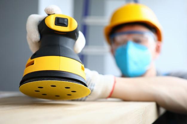 Il costruttore mascherato lucida la superficie di legno della levigatrice