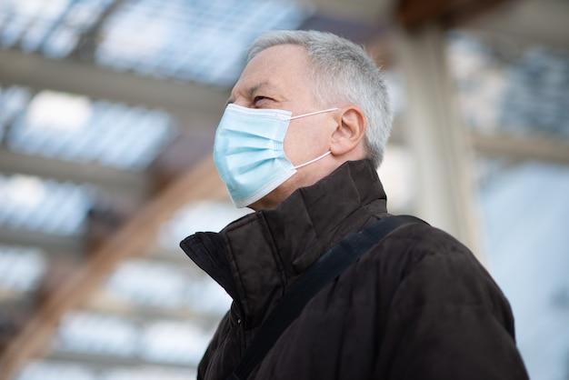 Uomo d'affari mascherato che cammina all'aperto per andare al lavoro, concetto di stile di vita della gente di coronavirus