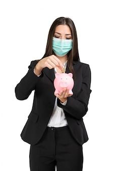Donna mascherata di affari che mette soldi in un porcellino salvadanaio, concetto di risparmio del coronavirus, isolato sulla parete bianca