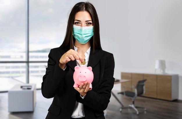 Donna di affari mascherata che mette soldi in un salvadanaio in un ufficio luminoso