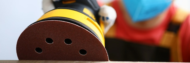 Il carpentiere mascherato macina il legno con la levigatrice. lo strumento viene utilizzato per lucidare e levigare le superfici in legno. metti in ordine il vecchio pavimento, il rivestimento in legno e tutti gli elementi interni. strumento per l'aggiornamento