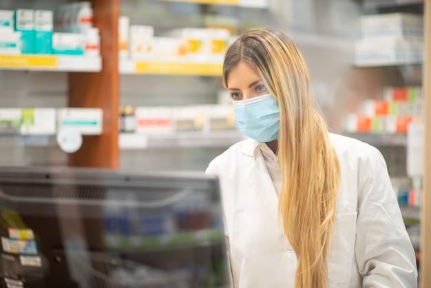 Cassiere mascherato in una farmacia, concetto di farmacista di coronavirus