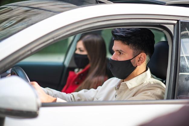 Coppia mascherata che viaggia in macchina, concetto di covid coronavirus