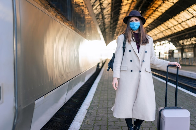 Turista mascherato alla stazione ferroviaria.