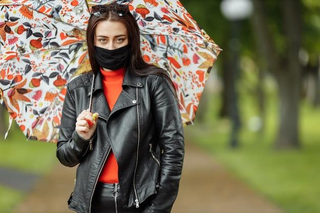 Una ragazza mascherata sta camminando lungo la strada