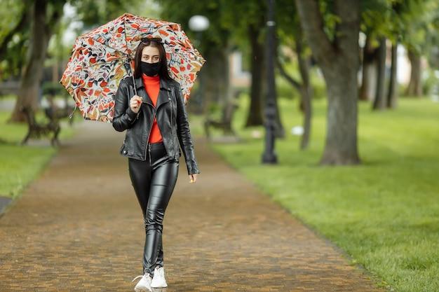 Una ragazza mascherata sta camminando per la strada. una ragazza con una maschera protettiva cammina nel parco con un ombrello sotto la pioggia. infezione da coronavirus covid-19.