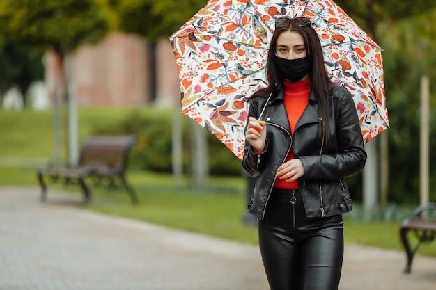 Una ragazza mascherata sta camminando per la strada. una ragazza con una maschera protettiva cammina nel parco con un