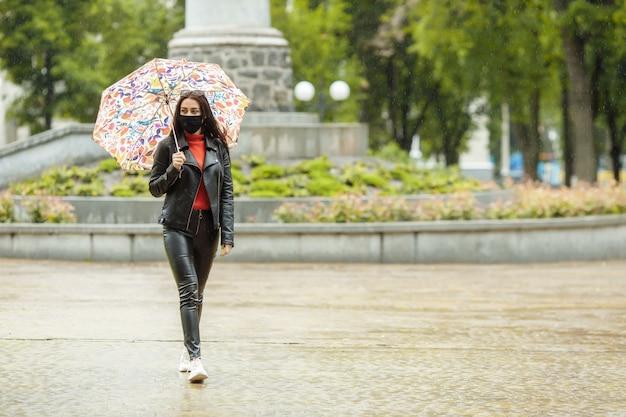 Una ragazza mascherata sta camminando per la strada