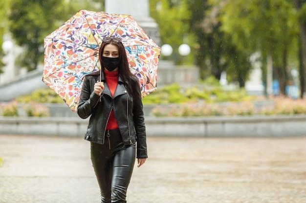 Una ragazza mascherata sta camminando per la strada.
