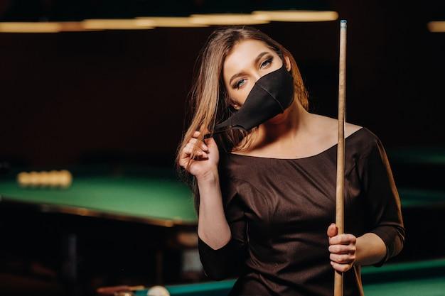 Ragazza mascherata in un club di biliardo con una stecca tra le mani.