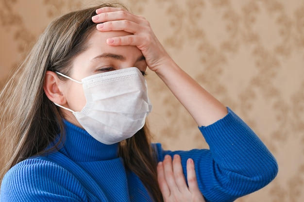Ragazza mascherata con mal di testa. avvicinamento. i primi segni di coronavirus.