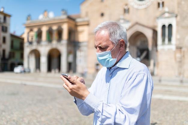 Uomo mascherato che utilizza il suo smartphone all'aperto in un grande quadrato europeo