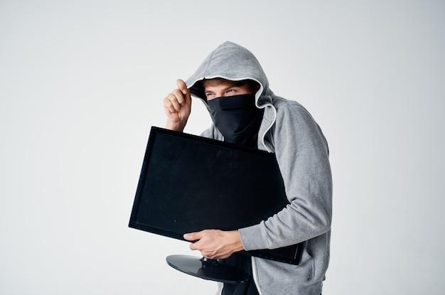 L'uomo mascherato con la felpa ruba lo schermo del computer