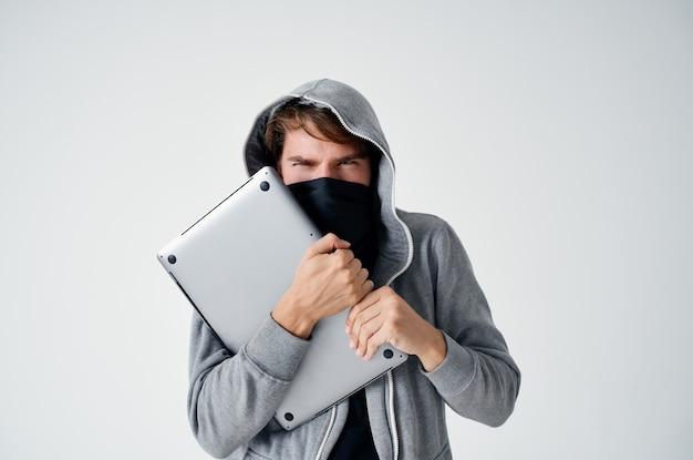 Un uomo mascherato con la felpa ruba il laptop