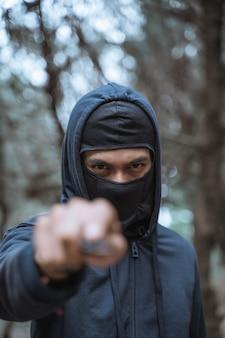 Uomo mascherato con un coltello che indossa abiti neri con occhi minacciosi della foresta