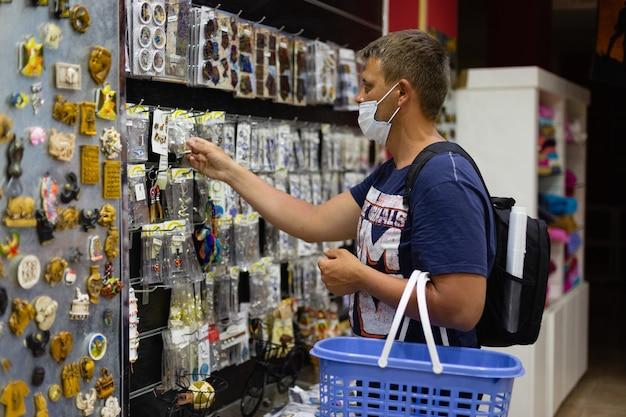 Uomo mascherato con cestino della spesa nel negozio un turista seleziona souvenir
